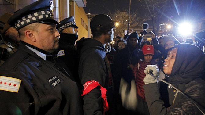 A protester chants a derogatory slogan towards Chicago policemen as protesters march down State Street in Chicago, Illinois