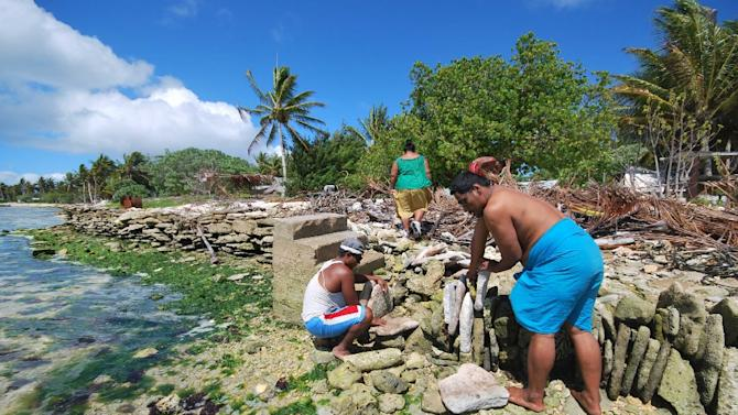 A community in Kiribati building a stone seawall at a coral atoll to protect its shore against a sea level rise
