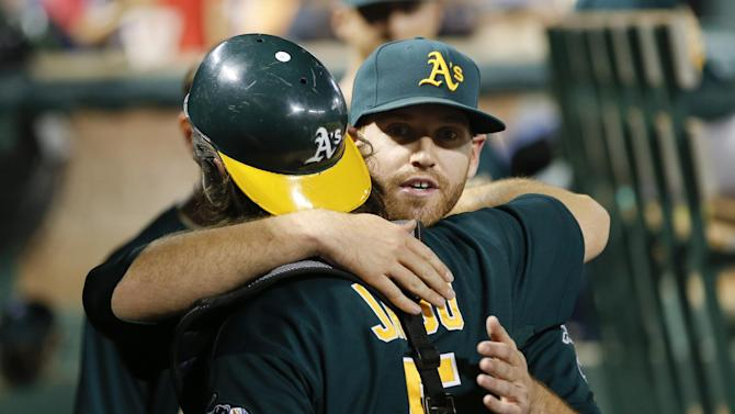 Oakland Athletics starting pitcher Dan Straily, right,  is hugged by catcher John Jaso, left, in the dugout after the seventh inning against the Texas Rangers during a baseball game, Tuesday, May 21, 2013, in Arlington, Texas. Straily allowed only two hits over seven innings. (AP Photo/Jim Cowsert)