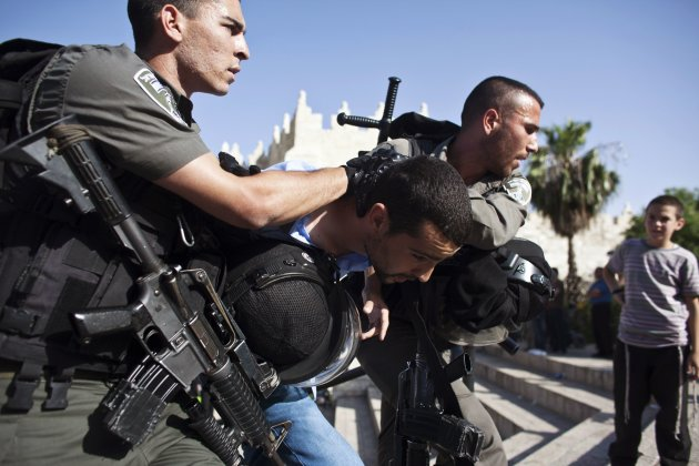 Israeli border police officers detain a Palestinian who protested in front of the Damascus Gate outside Jerusalem's Old City