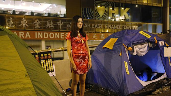 "A pro-democracy student protester displays a yellow sticker reading, ""I want genuine universal suffrage"" on her dress during a Halloween celebration in the areas occupied by protestors outside government headquarters in Hong Kong's Admiralty, Saturday, Nov. 1, 2014. Hong Kong student protest leaders are considering visiting Beijing while it hosts a major Asian summit next week to press their demands for greater democratic reforms. (AP Photo/Kin Cheung)"