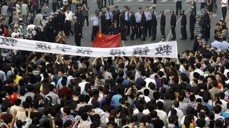Residents march in Zhejiang province's Ningbo city, protesting the proposed expansion of a petrochemical factory on Sunday, Oct. 28, 2012. Thousands of people in the city clashed with police Saturday while protesting the plan that they say would spew pollution and damage public health, townspeople said. (AP Photo/Ng Han Guan)