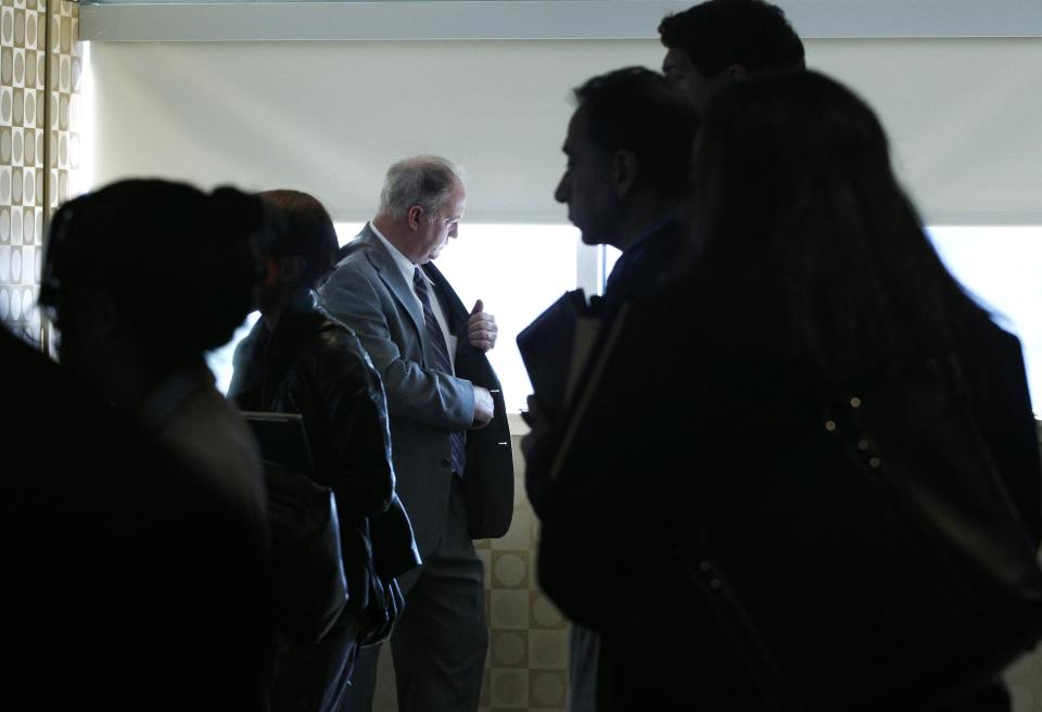 In this Oct. 17, 2011 photo, a man pauses by a window as job seekers wait to get information and drop off resumes during a job fair in Boston. Fewer people likely applied for unemployment benefits last week, suggesting the job market may be improving slightly. (AP Photo/Elise Amendola)