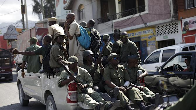 Unidentified men in military style clothes and holding guns drive around Port-au-Prince, Haiti