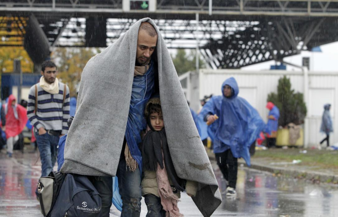 Migrants cover themselves with a blanket as they walk into Slovenia from Trnovec