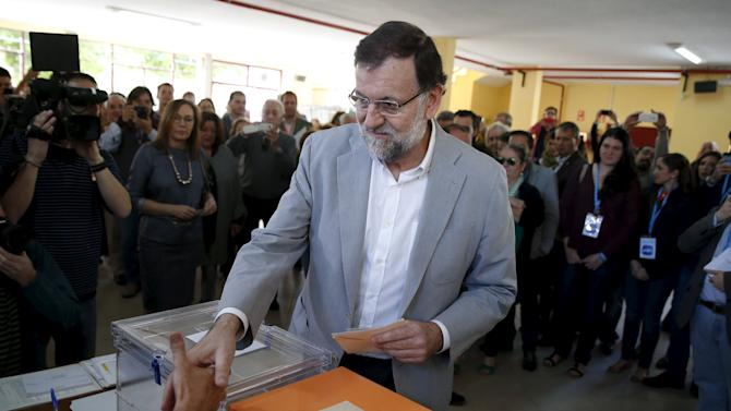 Spain's Prime Minister Rajoy shake hands with members of a polling station during regional and municipal elections in Madrid