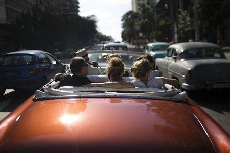 Tourists take a ride in a convertible car in Havana