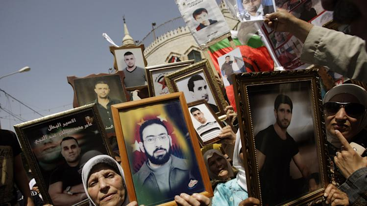 Palestinians hold pictures of relatives held in Israeli jails during a protest to mark Prisoner Day in the West Bank city of Jenin, Thursday, April 17, 2014. (AP Photo/Mohammed Ballas)
