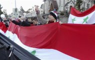 A pro-Assad demonstrator gestures as he holds the Syrian national flag in front of the venue where the Syria peace conference is held, in Montreux January 22, 2014. REUTERS/ Kinda Makieh