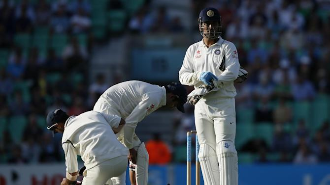 India's captain MS Dhoni, right, waits as his player pad up for close fielding during the second day of the fifth Test cricket match against England at Oval cricket ground in London, Saturday, Aug. 16, 2014. (AP Photo/Alastair Grant)
