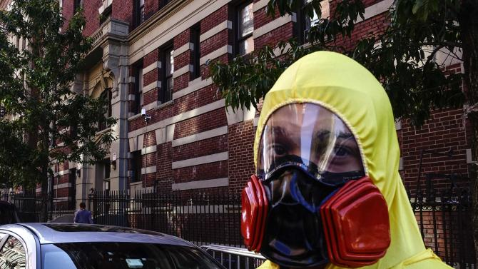 A man wearing personal protective equipment (PPE) as a Halloween costume, stands in front of the building where Dr. Craig Spencer lives in New York