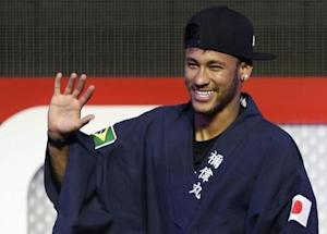 """Brazilian soccer player and Barcelona forward Neymar waves as he wears """"yukata"""" after receiving it as a souvenir from the organizer during a fan event in Tokyo"""