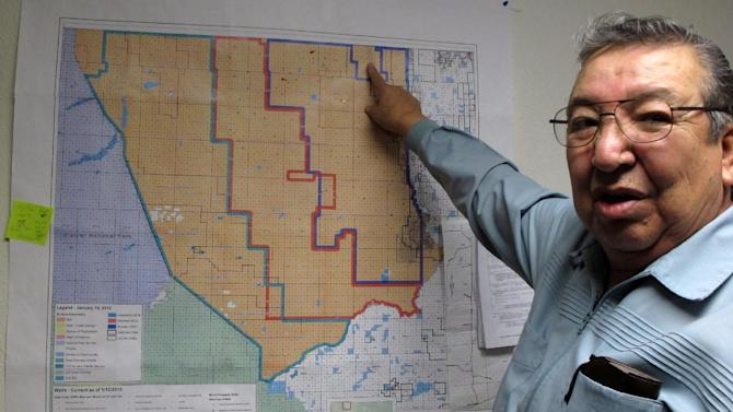 This Dec. 12, 2012 Blackfeet assistant oil and gas director Ron Cross Guns points to a map showing oil and gas development on the reservation, in Browning, Mont. Glacier National Park officials are concerned about the effects of development on the reservation, and are asking for an in-depth study on the environmental impacts. Blackfeet tribal officials say they are complying with all requirements before drilling and they bristle at the suggestion they can't develop their resources safely. (AP Photo/Matt Volz).