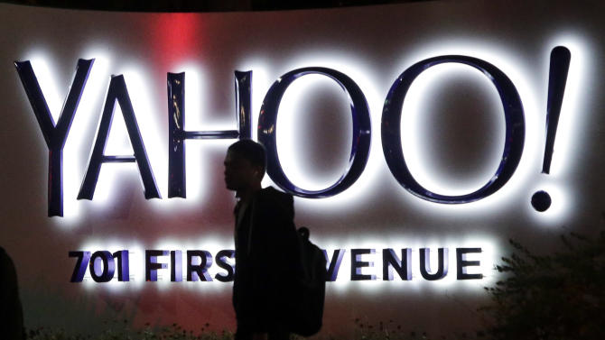 In this Nov. 5, 2014 photo, a person walks in front of a Yahoo sign at the company's headquarters in Sunnyvale, Calif. Yahoo reports quarterly financial results on Tuesday, Jan. 27, 2015. (AP Photo/Marcio Jose Sanchez)