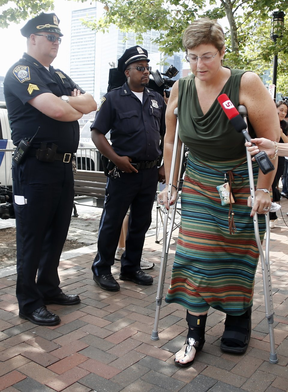 Boston Marathon bombing victim Karen Brassard makes her way into the federal courthouse for the arraignment of bombing suspect Dzhokhar Tsarnaev Wednesday, July 10, 2013, in Boston. The April 15 attack killed three and wounded more than 260. The 19-year-old Tsarnaev has been charged with using a weapon of mass destruction, and could face the death penalty. (AP Photo/Winslow Townson)