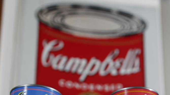 In this photograph taken Aug. 24, 2012, new limited edition Campbell's tomato soup cans with art and sayings by artist Andy Warhol are displayed in front of an original Warhol Pop Art painting from the 1960's in the boardroom at Campbell Soup Company in Camden, N.J. Campbell plans to introduce the special-edition cans of its condensed tomato soup bearing labels reminiscent of the pop artist's paintings at Target stores starting Sunday, Sept. 2, 2012. (Photo/Mel Evans)