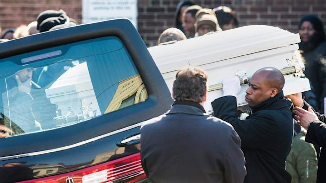 Pallbearers put the casket of three-year-old Elijah Marsh into the hearse following his funeral in Toronto