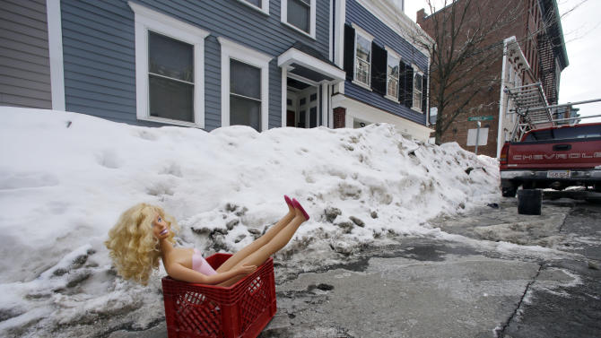 In this Feb. 23, 2015 photo, a fashion doll in a milk crate saves a parking space on a residential street in South Boston. Officials typically turn a blind eye to the lawn chairs, orange cones and assorted bric-a-brac Bostonians use to reserve a parking space after clearing it of snow. That ends Monday, March 2, 2015, with an order from City Hall to remove space savers, reigniting the ugly parking wars that have pitted neighbor against neighbor. (AP Photo/Elise Amendola)