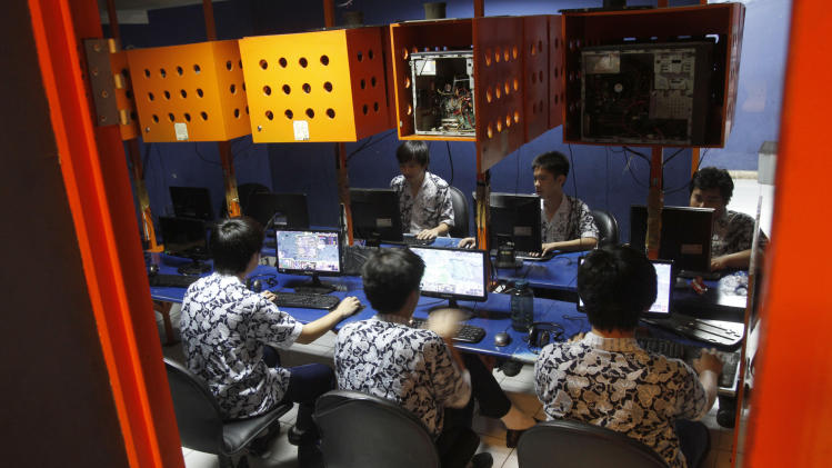 In this Friday, Oct. 19, 2012 photo, Indonesian students browse at an internet cafe in Jakarta, Indonesia. There are growing numbers of incidents involving internet social media networks being used as a mean for children trafficking in Indonesia, at least eight reported this month alone of young girls being abducted and enslaved by men who approached them randomly on Facebook, raising concerns that the overall number of trafficked children remains grossly underestimated in the sprawling archipelago of 240 million. (AP Photo/Tatan Syuflana)