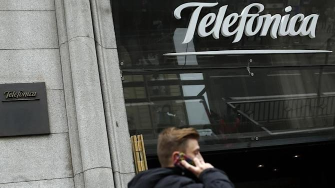 A man talks on a mobile phone as he walks past Spanish telecom group Telefonica flagship store in central Madrid