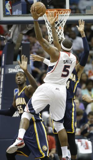 Atlanta Hawks small forward Josh Smith (5) shoots against Indiana Pacers small forward Paul George, right, and Indiana Pacers center Roy Hibbert (55) during the first half in Game 3 of their first-round NBA basketball playoff series, Saturday, April 27, 2013 in Atlanta. (AP Photo/John Bazemore)