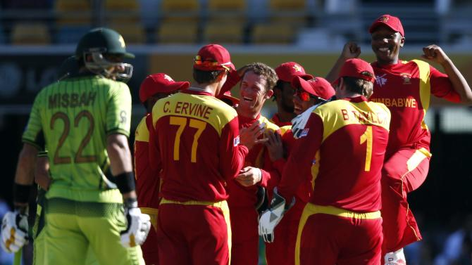 Pakistan's captain Misbah-ul-Haq reacts as Zimbabwe's Sean Williams celebrates with team mates after he bowled Shahid Afridi for a duck during their Cricket World Cup match at the Gabba in Brisbane
