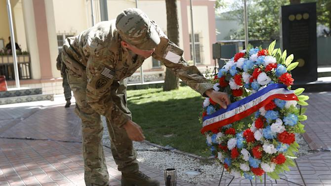 A U.S. soldier prepares a wreath of flowers during a ceremony to commemorate Memorial Day in Kabul