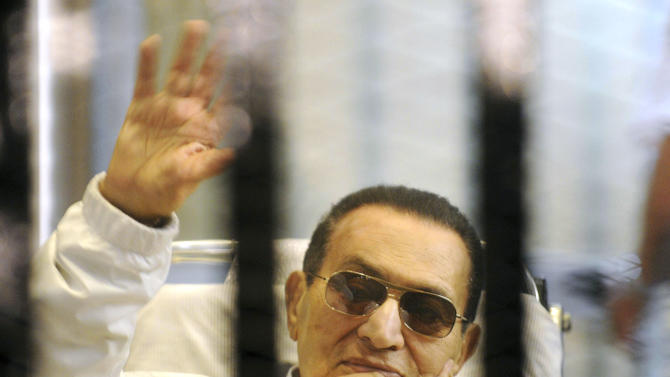 FILE - In this Saturday, April 13, 2013 file photo, former Egyptian President Hosni Mubarak waves to his supporters from behind bars as he attends a hearing in his retrial on appeal in Cairo, Egypt. Officials say an Egyptian court has ordered the release of ex-President Mubarak, but it's not immediately clear whether the prosecutors will appeal the order. (AP Photo, File)
