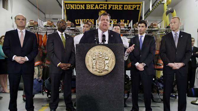 """Bob Martin, left, Commissioner New Jersey Department of Environmental Protection, Richard E. Constable III, second left, Commissioner New Jersey Department of Community Affairs, Marc Ferzan, second right, who manages the state's Superstorm Sandy Recovery efforts, and Ken Kobylowski, right, Commissioner New Jersey Department of  Banking and Insurance look on as Gov. Chris Christie addresses a gathering of residents and others in Union Beach, N.J., Tuesday, Feb. 5, 2013. Christie said Tuesday the National Flood Insurance Program's handling of claims in New Jersey """"has stunk,"""" complaining that the program has been far too slow to resolve claims from Superstorm Sandy, with 70 percent of cases unresolved three months after the disaster. (AP Photo/Mel Evans)"""