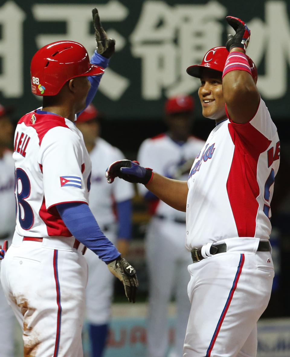 Cuba's leftfielder Alfredo Despaigne, right, celebrates with teammate Alexei Bell at home after hitting a three-run homer off Japan's pitcher Takeru Imamura in the eighth inning of their World Baseball Classic first round game in Fukuoka, Japan, Wednesday, March 6, 2013. (AP Photo/Koji Sasahara)
