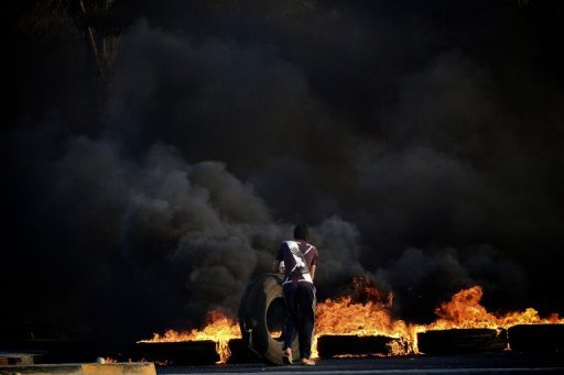A Bahraini Shiite protester in Sitra sets tyres on fire during clashes with police following a demonstration in solidarity with jailed Bahraini activist on September 3. A Bahrain court on Tuesday upheld jail terms against 13 leading opposition figures, including seven facing life in prison, over charges of plotting to overthrow the Gulf monarchy, lawyers said