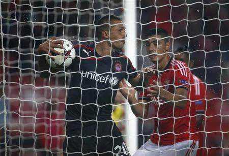 Benfica's Oscar Cardozo (R) tries to take the ball from Olympiakos' Jose Holebas after scoring a goal during their Champions League soccer match at Luz stadium in Lisbon October 23, 2013. REUTERS/Rafa
