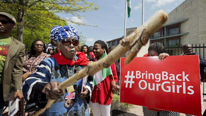 Mia Kuumba, of the District of Columbia, brandishes a wooden stick during a rally in front of the Nigerian embassy in northwest Washington, Tuesday, May 6, 2014, protesting the kidnapping of nearly 300 teenage schoolgirls, abducted from a school in the remote northeast of Nigeria three weeks ago. (AP Photo/Manuel Balce Ceneta)