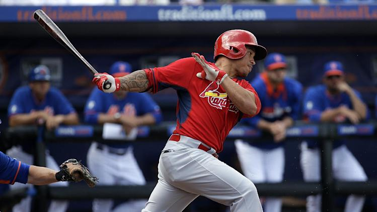 St. Louis Cardinals' Kolten Wong hits a single in the second inning of an exhibition spring training baseball game against the New York Mets, Wednesday, March 12, 2014, in Port St. Lucie, Fla
