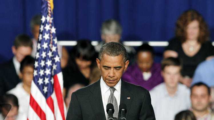 "President Barack Obama takes a moment of silence for the events in Colorado during a campaign stop in Fort Myers, Fla., Friday, July 19, 2012. Obama said the tragic movie theater shooting in Colorado that left 12 people dead is a reminder that life is fragile. He says the event ""reminds us of all the ways that we are united as one American family."" (AP Photo/Alan Diaz)"
