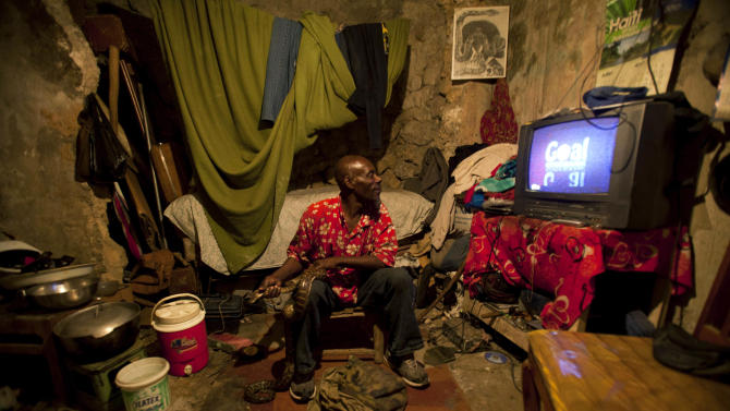 In this Jan. 24, 2013 photo, snake handler Saintilus Resilus watches a soccer game at his home while holding a snake, and a bag of more snakes lays at his feet, as he prepares for his street performances using snakes, for which he charges money, in Petionville, Haiti. Resilus is one of millions of people scrambling to get by in a country where the unemployment rate hovers around 60 percent and most get by on $2 a day. (AP Photo/Dieu Nalio Chery)