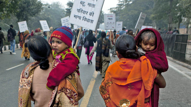 """Indian women carry their children as they march during a protest to mourn the death of a gang rape victim in New Delhi, India, Wednesday, Jan. 2, 2013. India's top court said it will decide whether to suspend lawmakers facing sexual assault charges as thousands of women gathered at the memorial to independence leader Mohandas K. Gandhi to demand stronger protection for their safety. The writing on the sign in foreground reads """" Daughter-in-law, daughter, mother are the ones who decide the fate of the family.""""(AP Photo/ Dar Yasin)"""