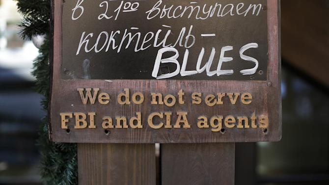 """A sign that says """"We do not serve FBI and CIA agents,"""" hangs outside a restaurant on the opening day of the 2014 Winter Olympics, Friday, Feb. 7, 2014, in Krasnaya Polyana, Russia"""