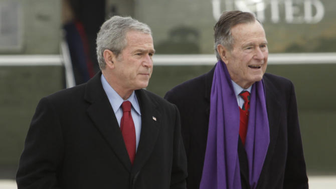 FILE - In this Dec. 26, 2008 file photo, President George W. Bush walks with his father, former President George H.W. Bush, at Andrews Air Force Base, Md. A criminal investigation is under way after a hacker apparently accessed private photos and emails sent between members of the Bush family, including both former presidents, according to reports Friday, Feb. 8, 2013. (AP Photo/Evan Vucci, File)
