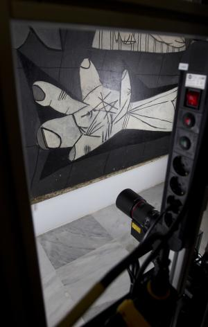 """A camera mounted on a mobile robot-like structure moves across Pablo Picasso's 'Guernica' painting at the Reina Sofia Museum in Madrid Tuesday Feb. 21, 2012. Experts have long been concerned about the health of Picasso's """"Guernica,"""" one of the world's most iconic paintings but one which is diagnosed as extremely delicate after a hectic life. A mobile, robot-like structure, which using advanced infrared and ultraviolet photographic technology, is taking thousands of microscopic shots of the painting to allow analysts to penetrate the work like never before and see its real condition. The mechanism has been constructed precisely so that the """"Guernica"""" is not endangered in any way by having to be moved to a conservation laboratory, where normally such investigative work would be done.  (AP Photo/Paul White)"""