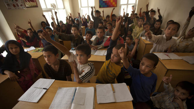 FILE - In this July 26, 2011 file photo, Afghan street children raise their hands to answer the question posed to them by their teacher at Ashiana centre in Kabul, Afghanistan. At least 250 million of the world's 650 million primary school age children are unable to read, write or do basic mathematics, according to a report Wednesday, Jan. 29, 2014, commissioned by UNESCO, the U.N. Educational, Scientific and Cultural Organization. It estimated that 14 countries had more than one million children out of school in 2011 including Afghanistan, China, Congo, Somalia, Sudan before its break-up, and Tanzania. (AP Photo/Dar Yasin, File)