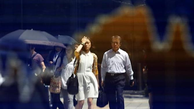 Pedestrians are reflected on a stock quotation board displaying a graph of the movement of Japan's Nikkei average outside a brokerage in Tokyo August 28, 2013. REUTERS/Yuya Shino