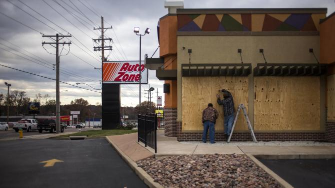 Workers board up a Taco Bell restaurant along W. Florissant in Ferguson
