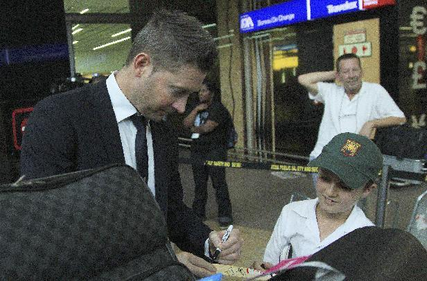 Australia's cricket captain Michael Clarke, left, signs a small cricket bat for unidentified fan during their arrival at OR Tambo International Airport in Johannesburg, South Africa, Wednesday, Ja