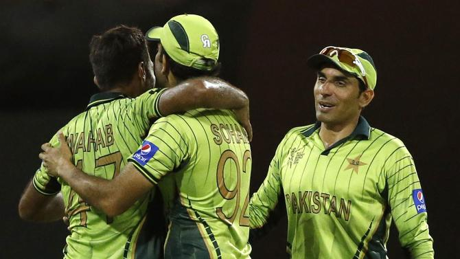 Pakistan's captain Misbah-ul-Haq celebrates with team mates Sohaib Maqsood and Wahab Riaz after winning their Cricket World Cup match against Zimbabwe at the Gabba in Brisbane