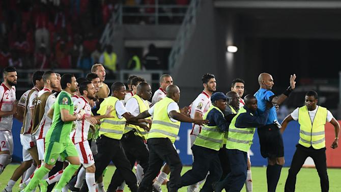 Security guards protect referee Rajindraparsad Seechurn (2nd-R) from Tunisia's players at the end of the 2015 African Cup of Nations quarter-final football match between Equatorial Guinea and Tunisia in Bata on January 31, 2015