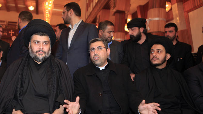 Catholic priest Ayser al-Yas, center, speaks as firebrand Shiite cleric Muqtada al-Sadr, left, visits Our Lady of Salvation church in Baghdad, Iraq, Friday, Jan. 4, 2013. Al-Sadr paid a visit Friday to a Baghdad church that was the scene of a deadly 2010 attack as well as one of the Iraqi capital's main Sunni mosques, an apparent overture to other religious groups as opposition mounts against his rival, Prime Minister Nouri al-Maliki. (AP Photo/ Karim Kadim)