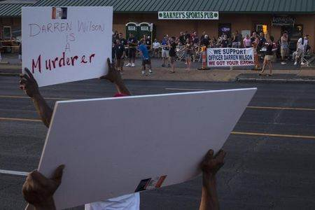 Demonstrators protesting the killing of unarmed teen Michael Brown hold placards towards Barney's Sports Pub where supporters of officer Darren Wilson gathered in St. Louis, Missouri