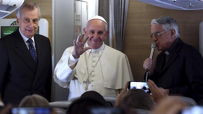 Pope Francis waves to the media aboard the papal plane while en route to Nairobi