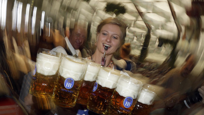 """A waitress carries beer mugs in the Hofbraeuhaus tent after the opening of the famous Bavarian """"Oktoberfest"""" beer festival in Munich, southern Germany, Saturday, Sept. 22, 2012.  The world's largest beer festival, to be held from Sept. 22 to Oct. 7, 2012, will see some million visitors. (AP Photo/Matthias Schrader) EDS NOTE - SHUTTER SPEED CAUSING BLUR"""